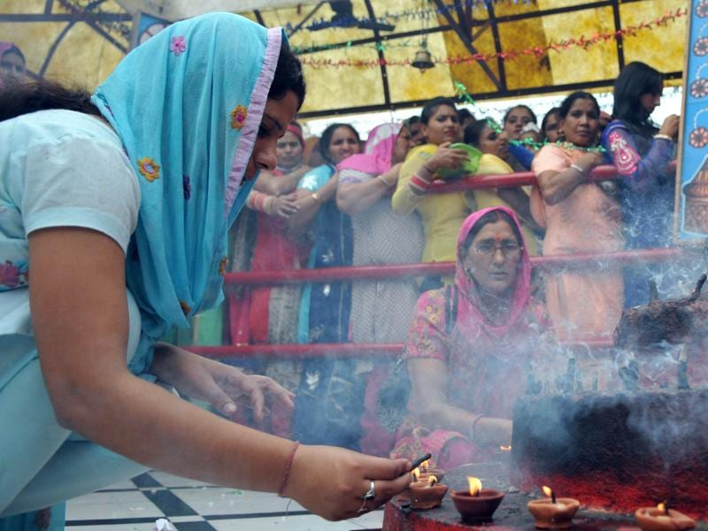 A devotee offering  prayers as other stands in queue on the first day of Navratras at  Bahu fort temple in Jammu on Tuesday. (Nitin Knaotra / HT)