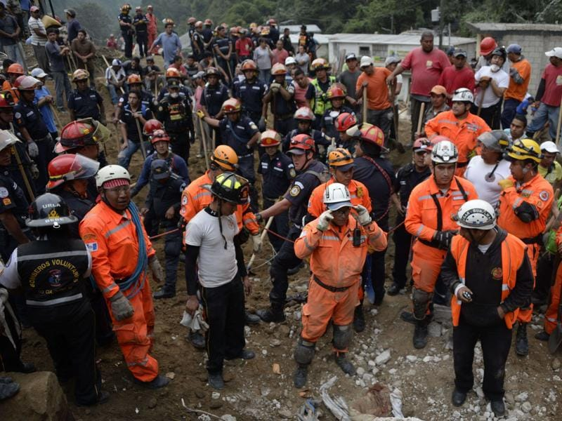 Firemen, rescuers, and volunteers take part in the rescue operations after a landslide late Thursday, following heavy rains, covered part of the village of El Cambray II, in Santa Catarina Pinula municipality, some 15 km east of Guatemala City, on October 2, 2015.  (AFP Photo)