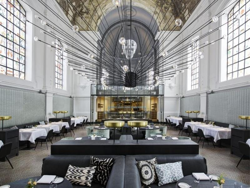 Designers at Piet Boon used the majestic backdrop of a former military hospital chapel to create a fine dining restaurant setting at The Jane in Antwerp. (AFP)