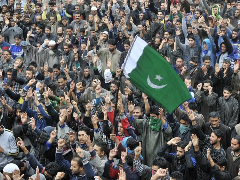A youngster carries Pakistani flag as others shout pro-freedom slogans during the funeral procession of Udhampur truck attack victim.  (Waseem Andrabi/HT)