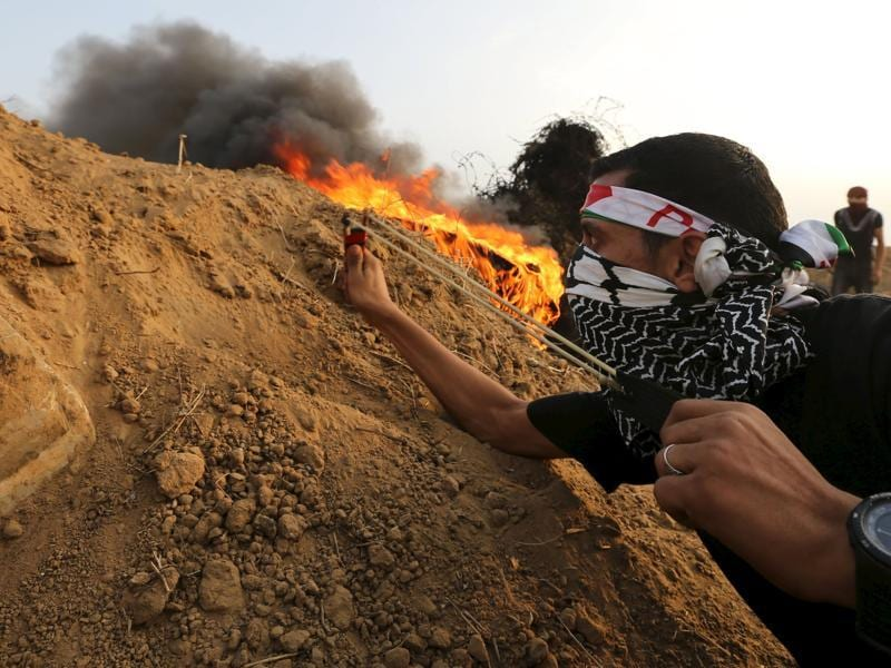 A Palestinian protester uses a slingshot to hurl stones towards Israeli troops during clashes near the border between Israel and Central Gaza Strip. (Reuters Photo)