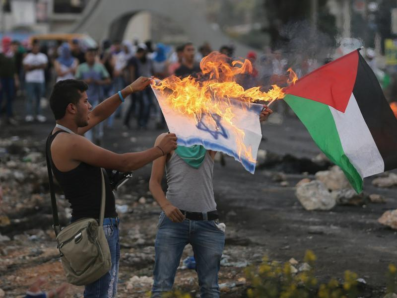 A Palestinian protester burns a replica Israeli flag as another holds a Palestinian flag during clashes with the Israeli troops near the Jewish settlement of Bet El, near the West Bank city of Ramallah. (Reuters Photo)