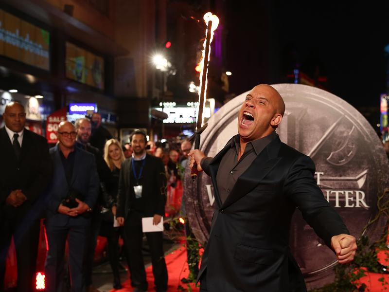US actor Vin Diesel runs towards photographers holding a flaming sword as he arrives on the red carpet to attend the European premiere of the film The Last Witch Hunter. (AFP)