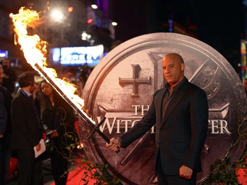 US actor Vin Diesel holds a flaming sword as he arrives on the red carpet to attend the European premiere of the film The Last Witch Hunter. (AFP)