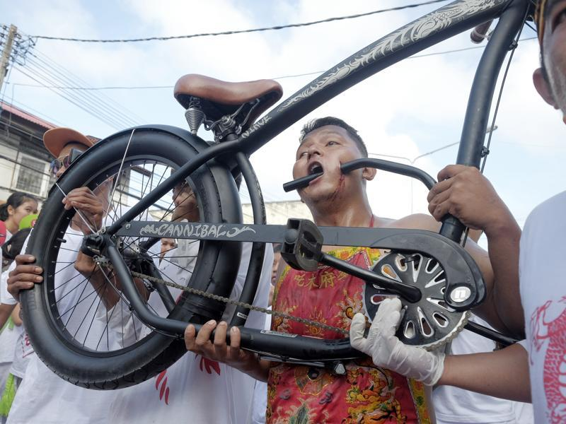A devotee has his cheek pierced with a bicycle as he and others walk in a street procession in Phuket, Thailand. The annual Vegetarian Festival is believed to bestow good fortune on those who practice the religious rites. (AP Photo/David Longstreath) (AP)