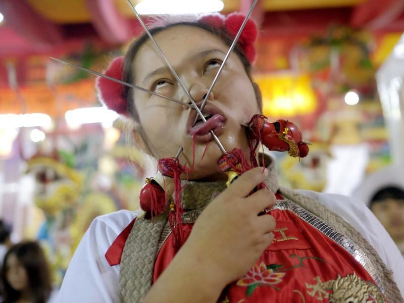 A devotee to the Chinese Shrine Ban Tha Rue in Phuket goes into a trance with her tongue and face pierced. The annual Vegetarian Festival and its accompanying sacred rituals are believed to bestow good fortune on those who practice the religious rites.  (AP Photo/David Longstreath) (AP)