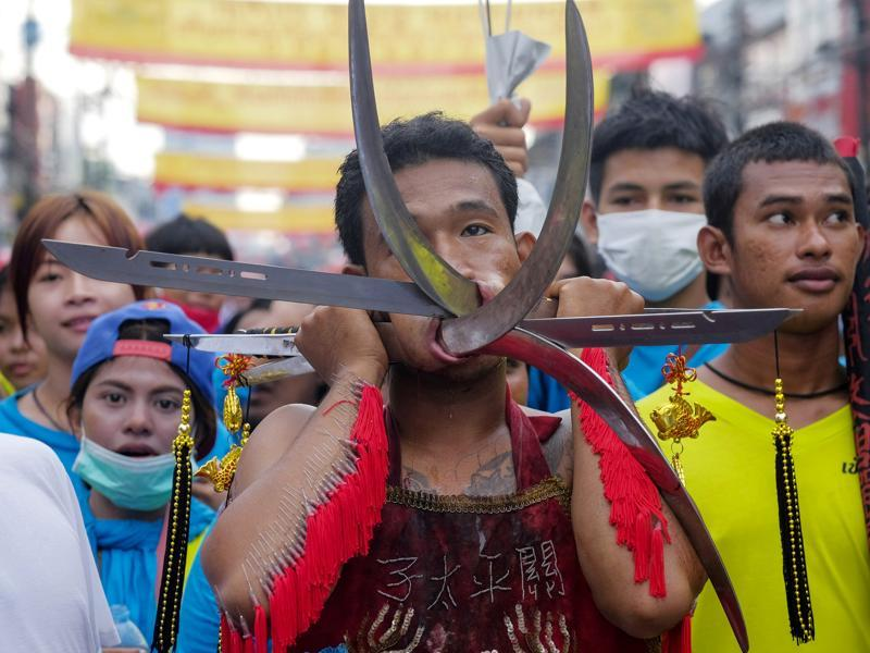 Men and women devotees during the festival work themselves into trances to have all manner of knives, daggers, swords or other items pierced through their cheeks. It is believed that they experience no pain while in the trance. (AP Photo/David Longstreath) (AP)