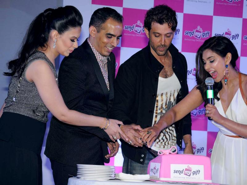 Do I need to eat this pink thingy? Hrithik Roshan looks on as Lisa Ray joins her at the launch of an e-commerce website in Bengaluru, on Oct 21, 2015. (IANS)