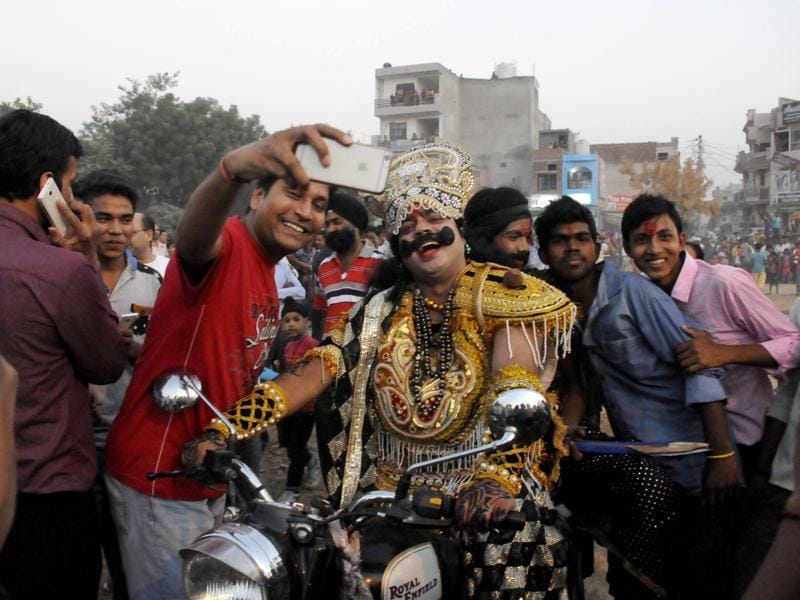 People take selfies with an artist playing the role of demon king Ravana as he arrives on a bike in Gurgaon's New Colony on the occasion of Dussehra on Thursday.  (Parveen Kumar/Hindustan Times)