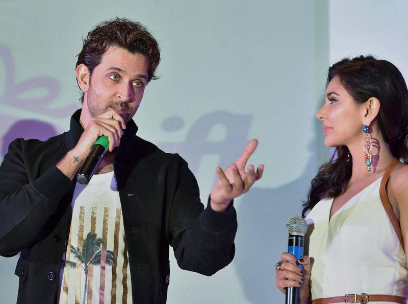 Og chuck everything, hand me a burger please? Hrithik Roshan speaks as Lisa Ray looks on during the launch of e-commerce website SendMyGift in Bengaluru on Wednesday.  (PTI)