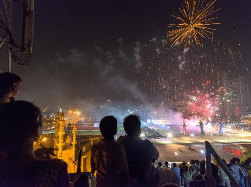 Residents from Old Delhi's Turkman Gate watch Dussehra festival celebrations from a rooftop near Ramlila grounds, just before giant effigies of Ravana, Kumbhakaran, and Meghnad were set ablaze in a symbolic act of victory of good over evil on Thursday.  (Gurinder Osan/ Hindustan Times)