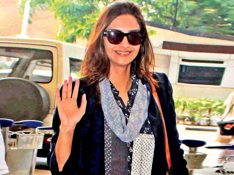Sonam Kapoor waves to fans at Mumbai airport.