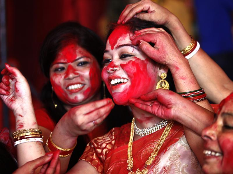 "Married Bengali women play  ""Sindoor Khela"", smearing vermillion on each other, during the final day of Durga Puja festivities in New Delhi.   (Ajay Aggarwal/Hindustan Times)"