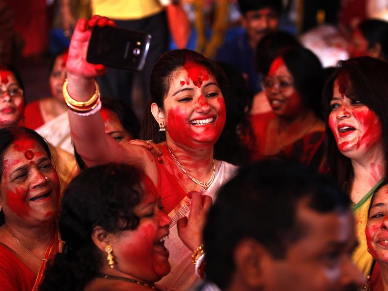 "Married Bengali women play  ""Sindoor Khela"", smearing vermillion on each other, during the final day of Durga Puja festivities in New Delhi. The five-day Durga Puja festival symbolises the triumph of good over evil. (Ajay Aggarwal/Hindustan Times)"