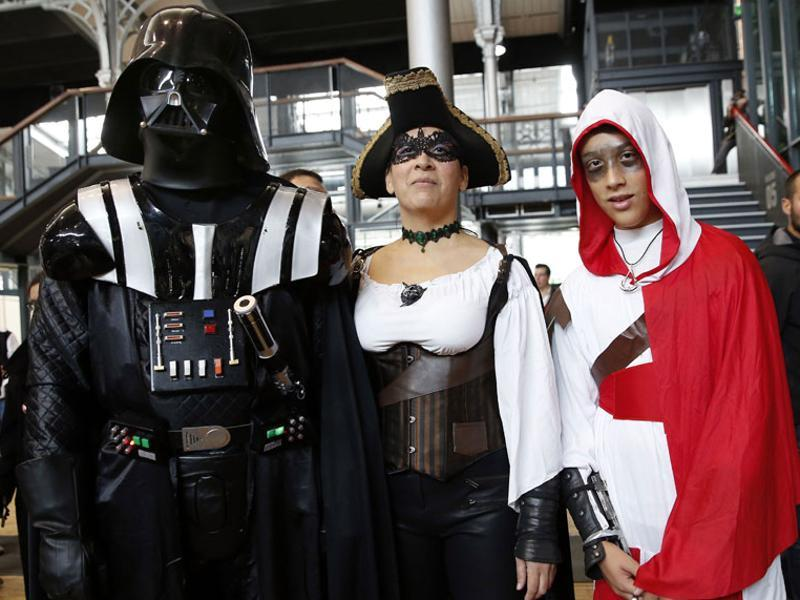 People dressed up as Star Wars character Darth Vader (left) and video game Assassin's Creed character (right) pose during the first Comic Con convention in Paris. (AFP)