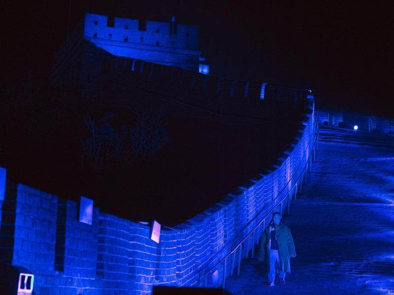 A worker walks along a section of the Great Wall of China lit by blue light to commemorate the 70th anniversary of the United Nations on the outskirts of Beijing, China. (AP Photo)