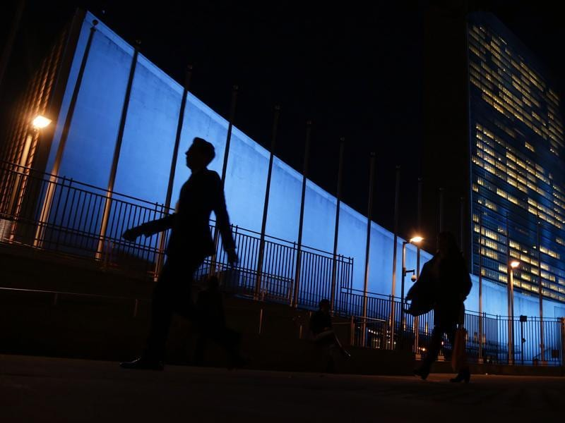 Pedestrians walk by United Nations Headquarters, lit up in blue light, a day in advance of the 70th Anniversary of the UN. (AP Photo)