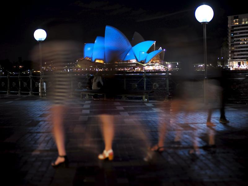 A group of women visiting Sydney's waterfront walk past the Sydney Opera House illuminated in blue.  Around 200 iconic monuments will be lit up in blue, the official colour of the United Nations, as part of a global campaign to commemorate its 70th anniversary.  (REUTERS Photo)