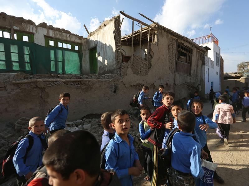 Afghan school boys tour the neighborhood to look at damaged houses. At least 70 people, including 12 Afghan girls, were killed in the earthquake. (AP)