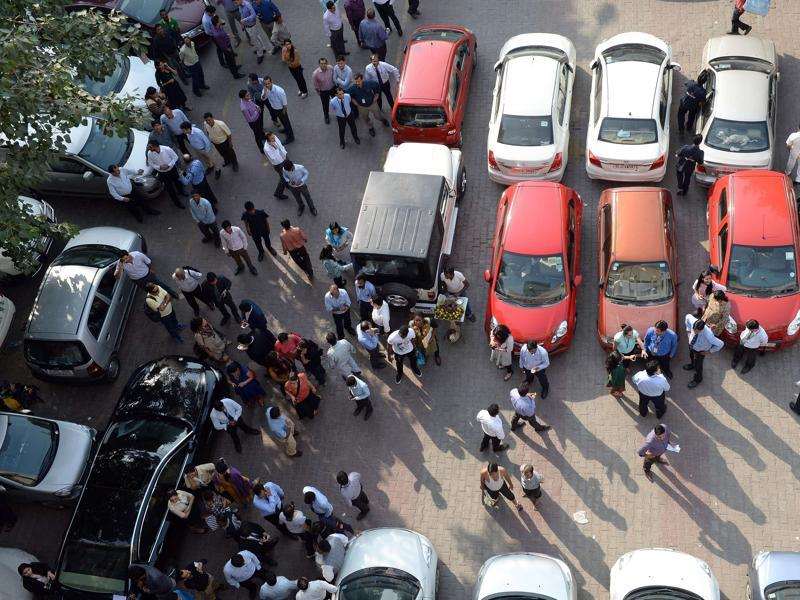 Office workers stand in an open area in a carpark following an earthquake in New Delhi.  A strong earthquake lasting almost a minute was felt in New Delhi on October 26, with buildings shaking in the centre of the Indian capital.  (AFP)