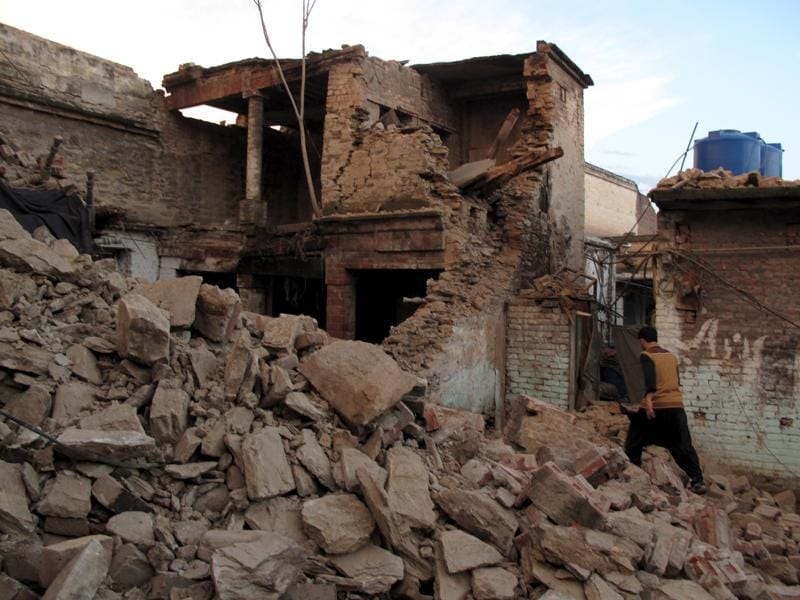 A resident walks past the rubble of a house after it was damaged by an earthquake in Mingora, Swat, Pakistan. (REUTERS)