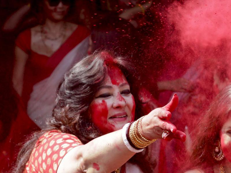 Bollywood actor and Indian lawmaker Moon Moon Sen, throws vermillion towards spectators during 'Sindoor Khela' or play of vermillion, a ritual during the Durga Puja festival in Kolkata, India , Sunday, Oct. 25, 2015.  (AP Photo)