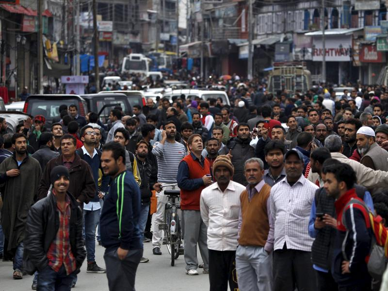 People stand on a road after vacating buildings following an earthquake in Srinagar. (REUTERS)