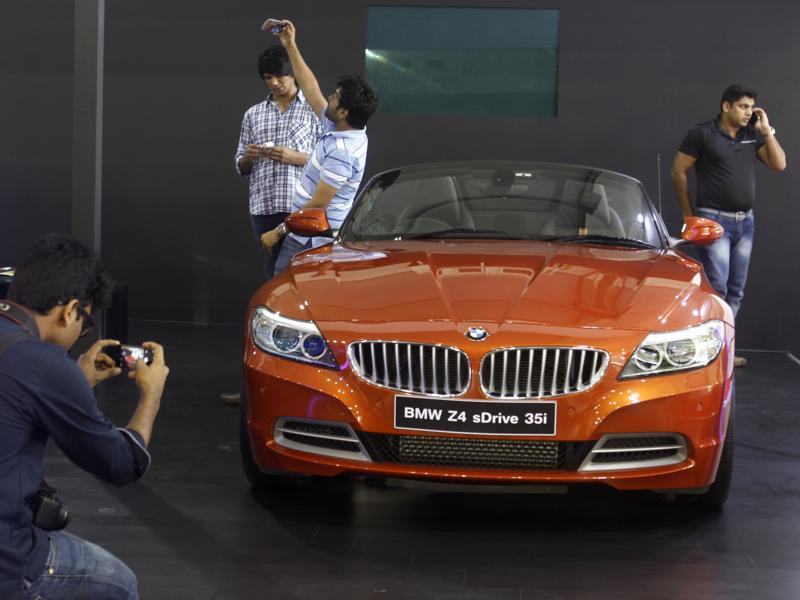 Dream car clicks: A man poses with a BMW at the expo. (satish Bate/HT)