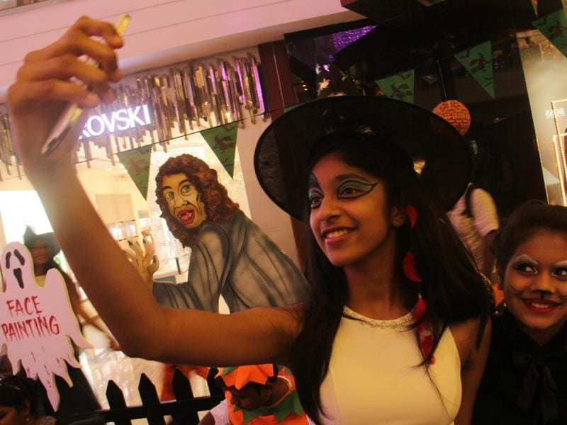 Children take a selfie after getting their faces painted during the Halloween party in Lower Parel, Mumbai, on Friday. (Pramod Thakur/HT photo)