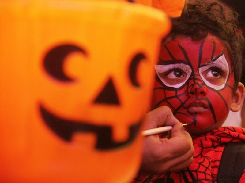 A child gets a Spiderman mask painted on his face at the Halloween bash at a mall in Lower Parel, Mumbai, on Friday. Halloween is celebrated in many countries on October 31, the eve of All Saints Day. Festivities on this day include carving pumpkins, dressing up in scary costumes, watching horror films and playing pranks.  (Pramod Thakur/HT photo)