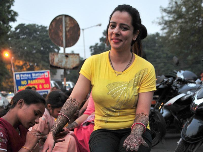 A heena artist applying Mehndi on the hands of women on the eve of karva chauth in sector 22 market in Chandigarh on Thursday. (Ravi Kumar/ HT photo)