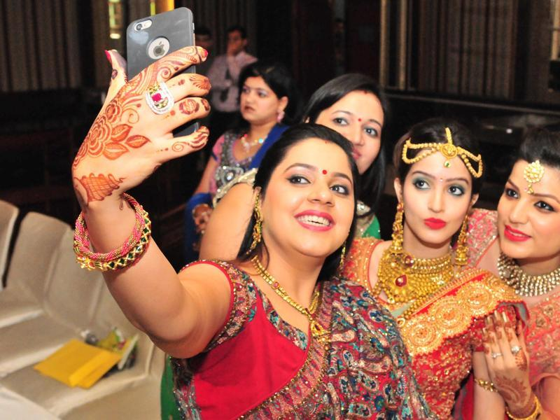 Selfie sessions: With new accessories and henna on their hands,  women taking selfie during the celebrations of Karva Chauth at hotal Regent Park in Jalandhar, on Friday. (Pardeep Pandit/HT Photo)