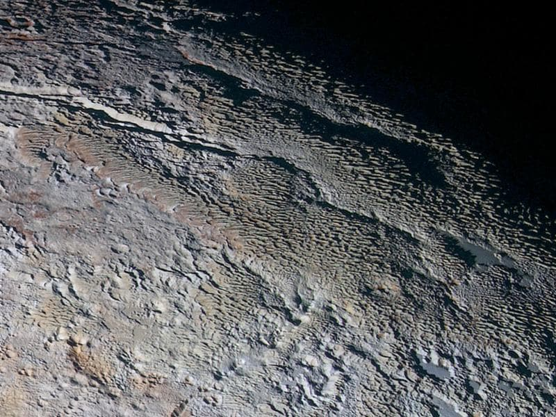 The Tartarus Dorsa Mountains: Rounded and bizarrely textured mountains, informally named the Tartarus Dorsa, rise up along Pluto's day-night terminator and show intricate but puzzling patterns of blue-gray ridges and reddish material in between.  (NASA)