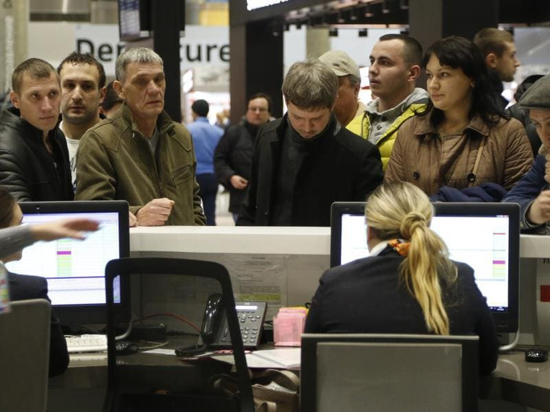 People gather at the airline information desk at of Russian airline Kogalymavia's desk at Pulkovo airport in St.Petersburg, Russia. (AP Photo)