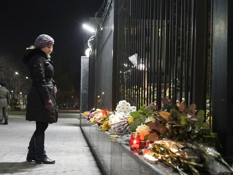 A Ukrainian woman pays tribute to victims of a Russian plane crash in front of the Russian Embassy in Kiev, Ukraine. (AP Photo)