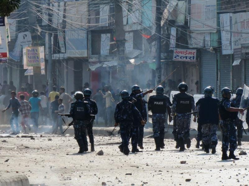 Nepalese police watch protesters throwing rocks during clashes near the Nepal-India border at Birgunj, some 90 km south of Kathmandu. (AFP Photo)