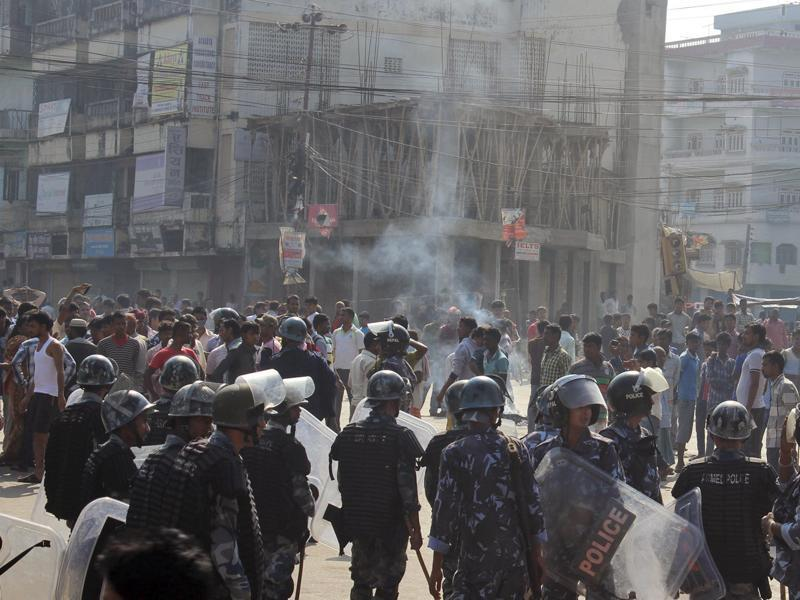 Ethnic Madhesi protesters stand near smoke from a tire set on fire by them, as Nepalese policemen stand guard near the Central Development Office at Birgunj, a town on the border with India, Nepal. (AP Photo)