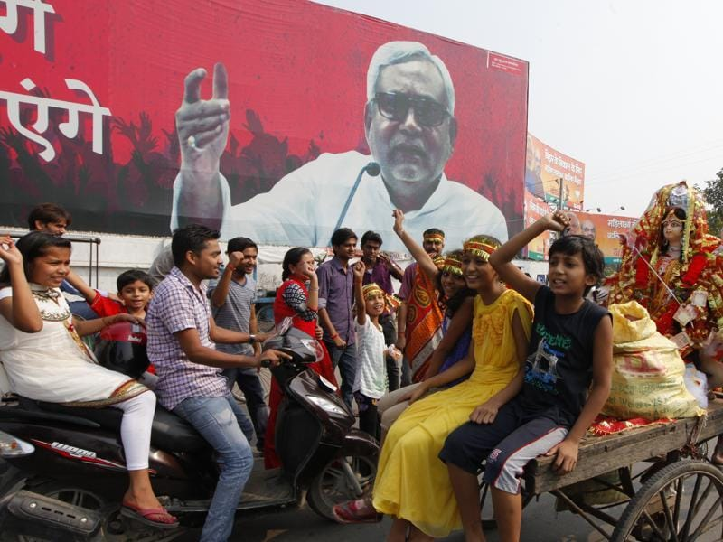 In poll-bound Bihar, an emphatic Nitish Kumar poster towers over children on their way to immerse idols during Durga Puja. (Arvind Yadav/ HT Photo)