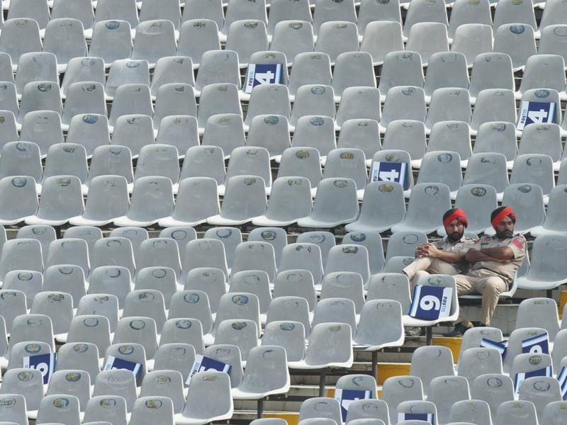Punjab Police officials on duty sit in empty stands at the PCA Stadium. (Gurpreet Singh/HT Photo)