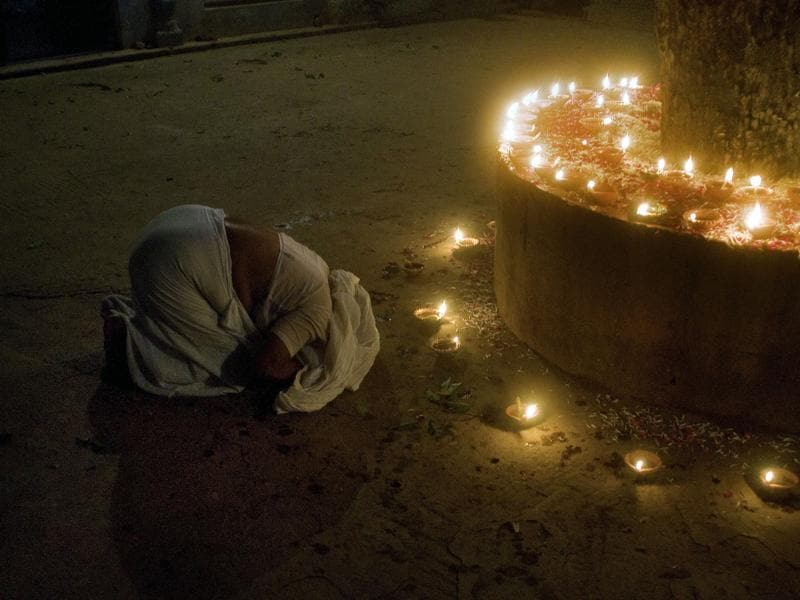 A widow prays before a sacred tree during Diwali celebrations at the Meera Sahabhagini Widows Ashram in Vrindavan. (AFP)