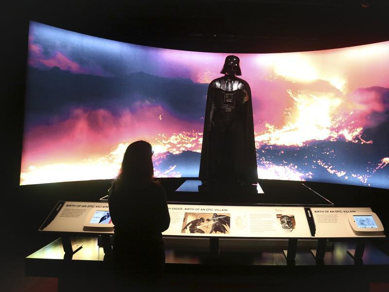 A woman looks at a Darth Vader costume used in Star Wars movies at the Discovery Store Times Square, New York. (REUTERS)