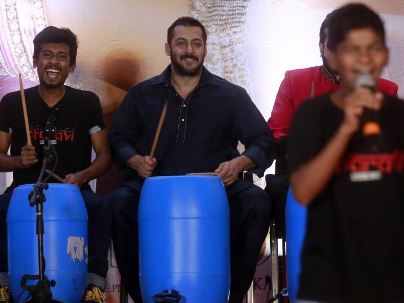 Salman Khan, center, beats on a percussion instrument made with recyclable items with children from Dharavi slum in Mumbai, on Wednesday, (AP)