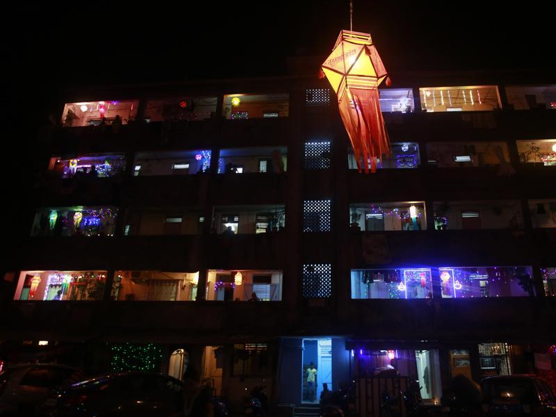 A tenement block housing mostly fishermen families is illuminated with lights during Diwali in Mumbai . (AP)