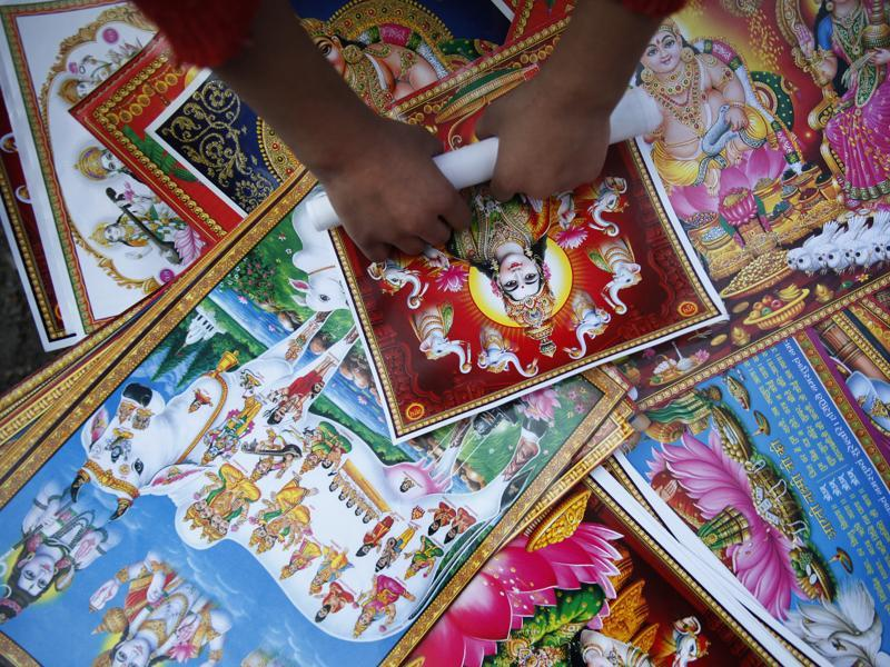 A Nepalese street vendor rolls a picture of Hindu goddess Lakshmi as he sells them during Tihar festival in Katmandu, Nepal, Thursday, Oct. 23, 2014. Hindus decorate their houses and worship Lakshmi, the goddess of wealth, during this festival of lights.  (AP)