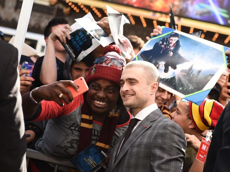 Actor Daniel Radcliffe poses with a fan for a photo at his star unveiling ceremony on the Hollywood Walk of Fame. (AFP)