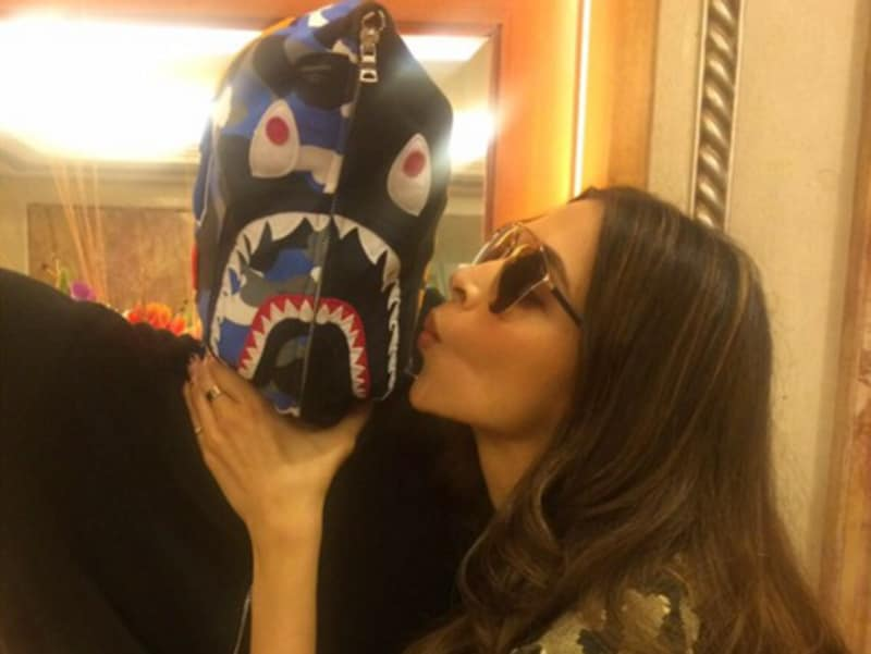 Gotta promote film, so what if it means kissing co-stars wearing masks? Deepika Padukone puts in another day at work. (Twitter)
