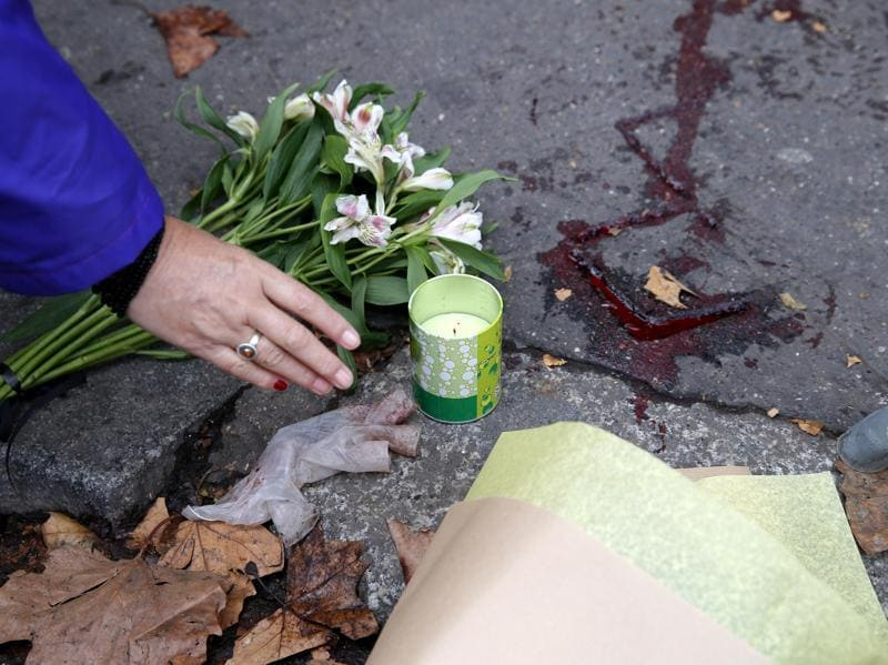 A woman places a candle outside the Bataclan concert hall, Saturday, Nov. 14, 2015 in Paris.  (AP Photo)
