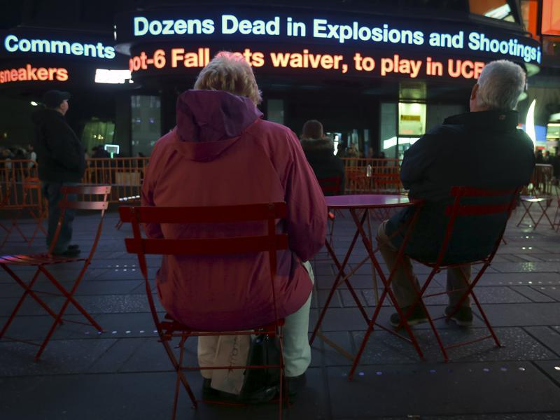People watch as a news ticker updates people with the news of the shooting attacks in Paris, in Times Square in the Manhattan borough of New York. (REUTERS)