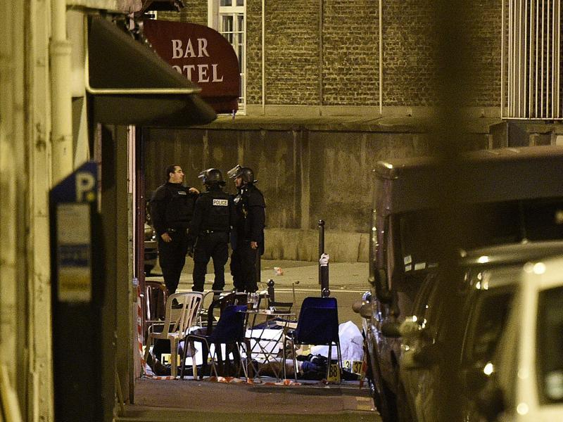 A victim lies on the ground covered by a white sheet following an attack at rue Bichat. (AFP)