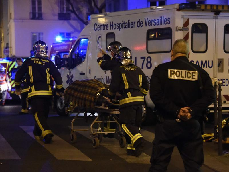 Firefighters evacuate an injured person near the Bataclan concert hall in central Paris. (AFP)